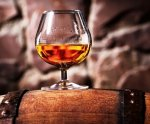 Glass of cognac on the old wooden barrel - JPEG - 47.7 ko